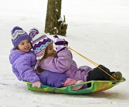 two little girls going down a hill on a sled together