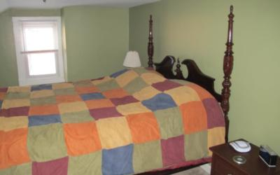 bed with quilt with colorful squares