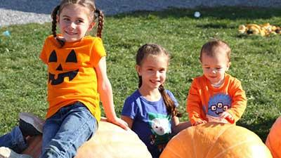 kids on pumpkins at ellms family farm