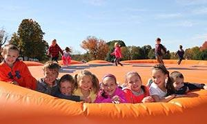 kids on orange jumping pillow