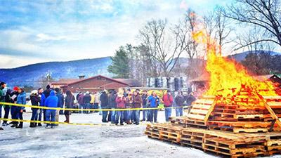 people standing around a bonfire made of pallets