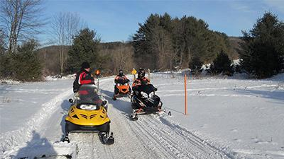 snowmobilers on a trail