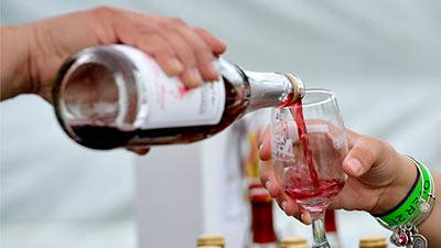 person pouring wine in a glass at an event