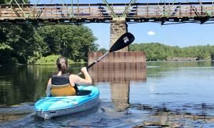 girl kayaking about to go under a bridge