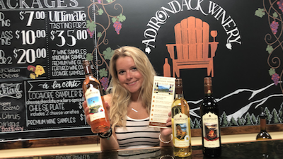 woman holding a bottle of Adirondack winery wine