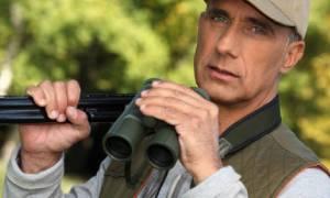 a hunter with gun and binoculars