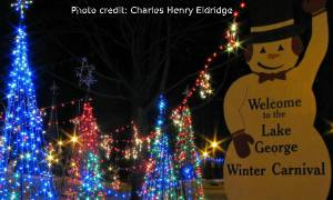 Lake George Winter Carnival snowman sign with lit up trees