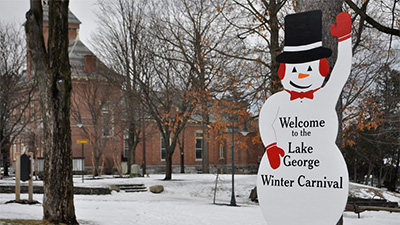 lake george winter carnival sign shaped like a snowman