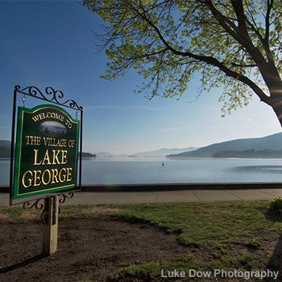 welcome to lake george village sign with lake and sun in the background
