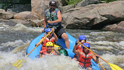 group whitewater rafting in a blue boat