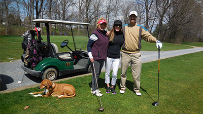 three people and a dog posing in front of a golf cart