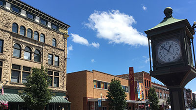 clock and buildings in downtown glens falls on a sunny day