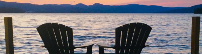 two adirondack chairs on a dock at sunset