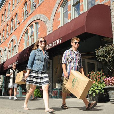 two friends walking while holding shopping bags