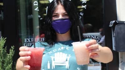 masked girl holding up wine slushies