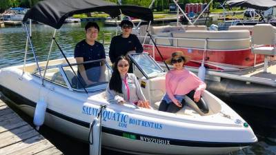 Asian family of four on rental boat at dock