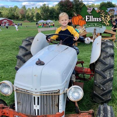 pumpkins at ellms farm and a boy on a tractor