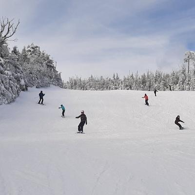 skiers and snowboarders going down a snowy hill