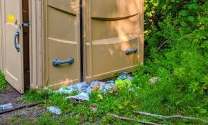 trash by porta potty in the woods