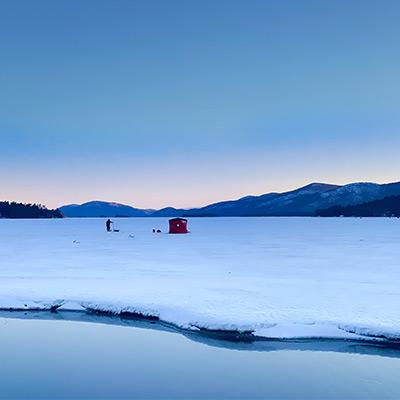 shanty and an ice fisherman on lake george at sunrise