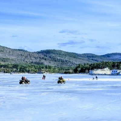 ATVs and people playing hockey on the frozen over lake