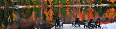 adirondack chairs on a dock with fall foliage