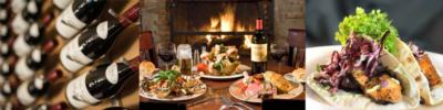 bottles of wine, fish tacos, and a fireside table with food and wine