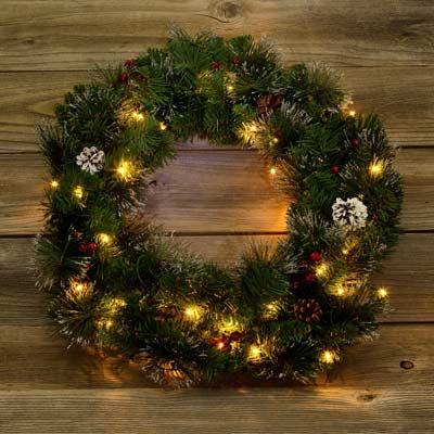adirondack style holiday wreath, fireplace, and snowy pine needles
