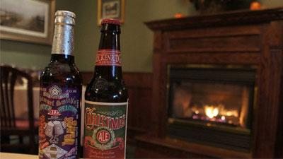 two beers in front of a roaring fire