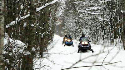 people riding snowmobiles in a line