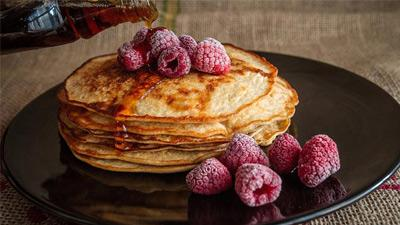 stack of pancakes with raspberries and maple syrup