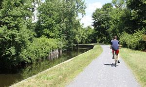 kid on bike riding by canal