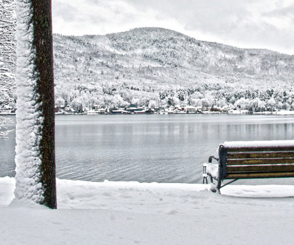 snowy bench next to lake george